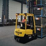 Operator moving automotive parts on a forklift truck