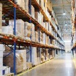 Inside a QCI warehouse showing a long warehouse storage isle with high bay racking. The tall racking is holding various automotive and aerospace e parts for warehouse storage. The bays are labelled on by location as per the stock management system.