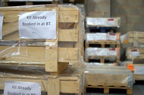 Kit crates for the rail industry stored inside a QCI warehouse. The crates are labelled up to help the warehouse storage operators know what the item is